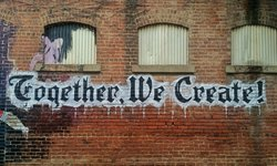 "Graffiti on a wall ""Together we create !"""